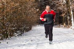 Pensionär som joggar i vintern Royaltyfria Bilder