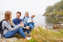 En pensionär och ett ungt vuxet par som tillsammans sitter vid en sjö arkivfoto