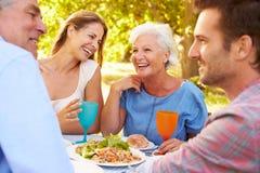 En pensionär och ett ungt vuxet par som tillsammans utomhus äter arkivbilder