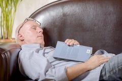En pensionär på en soffa sovande Royaltyfria Bilder