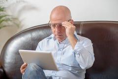 En pensionär ser en digital minnestavla Royaltyfri Fotografi