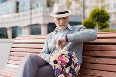 En pensionär sitter på en bänk som väntar på en kvinna De bör ha ett datum Arkivbilder