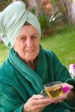 En pensionär tar en kopp av tisanen i en öppen brunnsortstudio Royaltyfri Fotografi