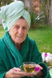 En pensionär tar hennes kopp av tisanen i en brunnsortstudio för öppen luft Royaltyfri Foto