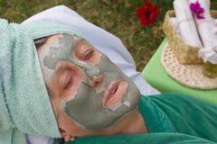 En pensionärs framsida täckas av den ansikts- maskeringen för lera close upp Royaltyfri Fotografi