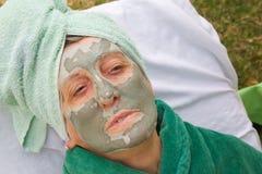 En pensionärs framsida täckas av den ansikts- maskeringen för lera close upp Arkivfoton
