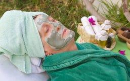 En pensionärs framsida täckas av den ansikts- maskeringen för lera close upp Royaltyfri Foto