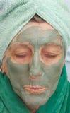 En pensionärs framsida täckas av den ansikts- maskeringen för lera close upp Arkivbild