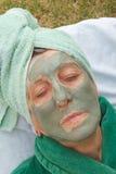 En pensionärs framsida täckas av den ansikts- maskeringen för lera close upp Fotografering för Bildbyråer