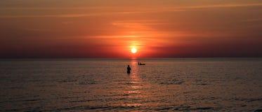 En person, ett fartyg, en solnedgång, en härlig bild arkivbilder