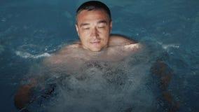En person kopplar av i det varmt badar Begrepp: Spa behandlingar, kroppmassage, simbassäng stock video