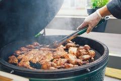 En person lagar mat kött för grillfesten för gäster, vänner Äta middag äta begrepp Matbuffé Sköta om att äta middag Royaltyfri Bild