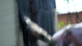 En person målar en träyttersida med en svart målarfärgborste lager videofilmer