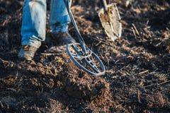 En person med en metalldetektor i ett fält, sökande för mynt, hobbyer Royaltyfri Bild