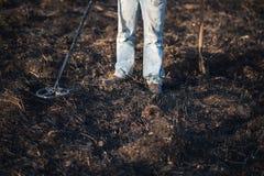 En person med en metalldetektor i ett fält, sökande för mynt, hobbyer Fotografering för Bildbyråer