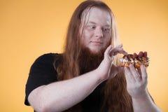 En person med mycket vikt äter en stor kaka royaltyfri fotografi