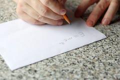 En person skriver en formel på papper med en blyertspenna arkivfoto