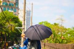 En person som använder ett paraply i sommar Arkivfoton