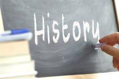 En person som skriver ordhistorien på en svart tavla Royaltyfria Foton