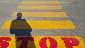 En person står i början av en övergångsställe, var det är det skriftliga stoppet och väntar på passagetiden, på gulingen arkivfilmer