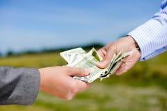 En persons hand som ger några pengar till andra Arkivbilder