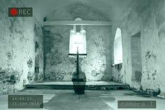 En Photoshop av en CCTV-bild av en med huva spöke som knäfaller bredvid ett kors i en avlagd kyrka arkivbild