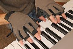 En pianist håller kamper kylan av vintern, genom att spela med fingerless handskar Fotografering för Bildbyråer