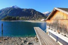 En pir för fartyg snubblar på Achensee sjön under vinter i Tirol, A Arkivbilder