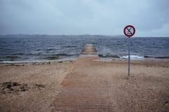 En pir leder in i vattnet, och ett tecken visar: förbjudit hoppa royaltyfria bilder