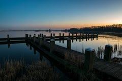En pir på en sjö med en väderkvarn i avståndet efter solnedgång arkivfoton