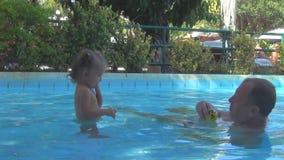 En piscina un bebé hermoso que lanza una bola amarilla al abuelo vuelo del espray de agua frente a un hombre, él atornilló u almacen de video