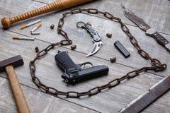 En pistol, kniv, metallkedja, takt, en hammare och flera cigaretter med en cigarettändare royaltyfri fotografi
