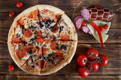 En pizza med champinjon-, salami-, peperoni- och olivlögner på lantliga för en tabell röda peppar tillsammans med, tomater, ost o arkivbild