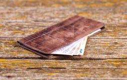 En plånbok, pengar och andra objekt är på tabellen av gamla bräden royaltyfri fotografi