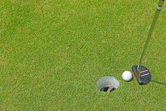 En plan head putterklubba för att en golfboll ska rulla inom en kopphol Arkivbild