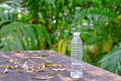 En plast- flaska av dricksvatten som skräpar ner på trätabellen med grön naturbakgrund för ett miljö- rengörande begrepp royaltyfri bild