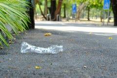 En plast- flaska av dricksvatten som skräpar ner på vägbottenvåningen på, parkerar med grön naturbakgrund för suddighet royaltyfri bild