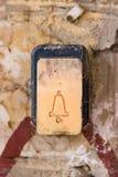 En plast- knapp med enfärgad doorphoneklocka med spårar av fäste skada och skrapor till en tegelstenvägg Tryckknapp royaltyfri fotografi