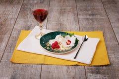 En platta av glass med bär och den dekorativa blomman Röd fruktfruktsaft och vitglass på en träbakgrund arkivfoto