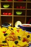 En platta av läckra tortillanachos med smältt ostsås, c Arkivbild