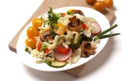 En platta av sallad med grönsaker, champinjoner och örter arkivbild