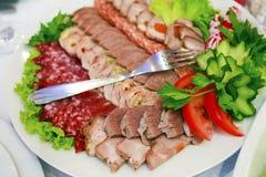 En platta av skinka, bacon, salami och korvar K?ttuppl?ggningsfat royaltyfria foton