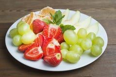 En platta med blandade frukter och skivade frukter Läckert mellanmål för ungar eller vuxen människa Jordgubbar, äpple, tangerinci royaltyfri foto