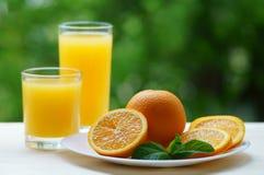 En platta med den skivade apelsinen och två exponeringsglas av fruktsaft Arkivfoton