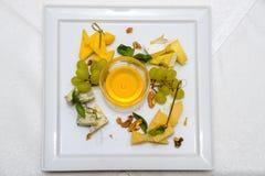 En platta med honung, ost, druvor och muttrar Royaltyfri Fotografi