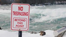En platta med en inskrift inget inkräkta Farligt för att simma och för att bo stället Det stormiga vattnet av floden arkivbild