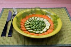En platta med morötter, zucchinin och gröna ärtor Fotografering för Bildbyråer