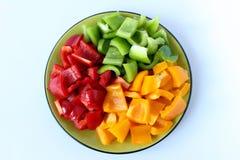 En platta som fylls med peppar i tre färger och snittet in i fyrkanter Royaltyfria Bilder