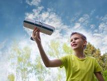 En pojke av det europeiska utseendet med ett flygplan mot himlen med moln Ljusa sinnesr?relser Kopiera utrymme arkivfoton