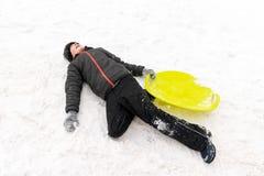 En pojke av sju år gammalt ligga på snön och rymma en grön plast- släde i hans hand Begrepp av vinteraktiviteter, rekreation arkivbild
